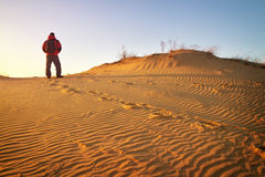 Sandy desert and man standing at a dune top. Sandy desert and man in winter clothes standing at a dune top Royalty Free Stock Images