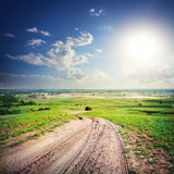Sandy dirt road in a green field Stock Image