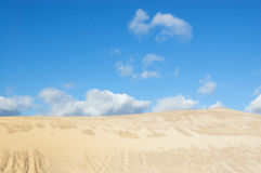 Sandy dune in city suburb. Sandy dune with traces of cars. The blue sky, white clouds royalty free stock image