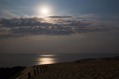 Sandy dunes with moon during nighttime Stock Images