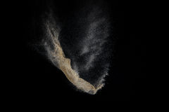 Sandy explosion isolated on black background. Abstract particles cloud. Texture element for design royalty free stock photo