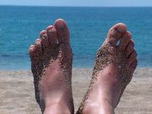Sandy feet. Young girls sandy feet on a beach royalty free stock image