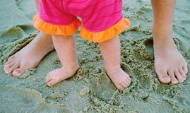 Sandy Feet. Little girl's feet inside her mother's feet at the beach Royalty Free Stock Photos