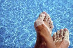 Sandy Feet. Sandy, suntanned feet with blue pool water as background Stock Photo