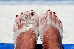 Sandy feet with painted toe nails on the beach Stock Images