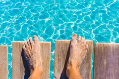 Sandy feet on the pier tropical turquoise sea Royalty Free Stock Photo