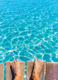 Sandy feet on the pier tropical turquoise sea Stock Images