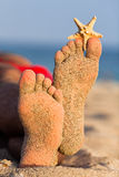 Sandy feet with starfish. Stock Photos