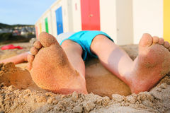 Sandy feet of a young boy lying on a beach Royalty Free Stock Image