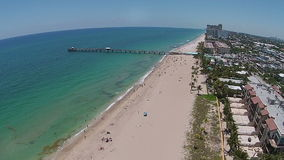 Sandy Florida beach and pier aerial view. Sandy beach and fishing pier in Florida seen from high above stock video