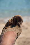 Sandy foot. Male foot on the beach, with toes partially covered with sand Royalty Free Stock Photo