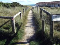 Sandy footpath to beach. A sandy footpath leading to a beautiful beach on a sunny summer day flanked with wooden and wired fencing Stock Image