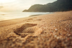 Sandy Footprint At Sunrise. A footprint on the beach while the sun is setting. Warm tropical colors stock photo