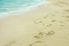 Sandy footprints on tropical beach stock photos