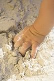 Sandy Hand. Babies hand playing in the sand Stock Image