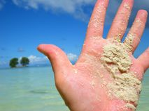 Sandy hand by tropical ocean Stock Photography