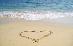 Sandy heart. Heart drawn in sandy beach with sea in background Royalty Free Stock Photo
