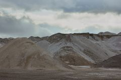 Sandy hills against the sky. Sandy hills against the background of a cloudy sky Stock Images
