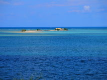 Sandy island in blue sea Stock Photos