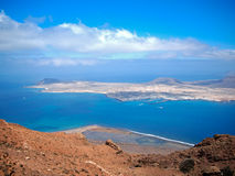 Sandy island with volcanoes and mountains in Atlantic Ocean. Aerial view from mountain slope. Yacht harbor and boats in strait. De Royalty Free Stock Images
