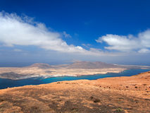 Sandy island with volcanoes and mountains in Atlantic Ocean. Aerial view from mountain slope. Yacht harbor and boats in strait. De Stock Photography