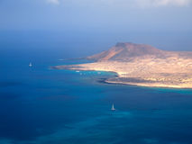 Sandy island with volcanoes and mountains in the deep blue Atlantic Ocean. Aerial view. Yacht harbor and boats in the strait. La G Royalty Free Stock Photos