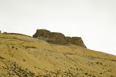 A sandy mountain hill with rocks royalty free stock images
