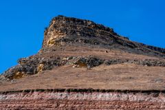 Sandy mountain with a sharp cliff and a small amount of vegetation against the blue sky stock photos