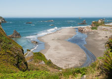 Sandy ocean beach with rock outcrops Royalty Free Stock Image