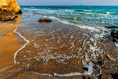 Sandy ocean shore with yellow rocks, sea waves with white foam. Ships on the horizon, a blue sky with white clouds on a summer evening, before sunset Royalty Free Stock Photography