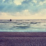 Sandy offshore. Concrete island in sea with sitting sea birds. Stone in ocean Stock Photography
