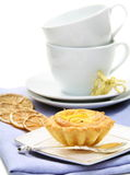 Sandy pastry with lemon filling and teacups. Stock Photos