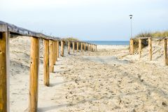 Sandy path leading to a beach. Wooden handrail, a single lamppost at the right, empty horizon Royalty Free Stock Image