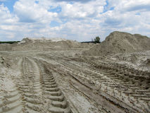 Sandy quarry with prints of tires of the tippers and a beautiful sky in the clouds above it. Heaps of white industrial sand and gentle blue sky above them Royalty Free Stock Photos