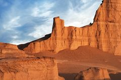Sandy red rocks against the blue sky with white clouds in the desert of Iran. A small silhouette of a man against the backdrop of. A grand nature royalty free stock image