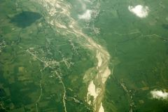 A sandy river bed among villages and green fields, view from a great height. white clouds above the ground. aerial photography. Sandy river bed among villages stock photography