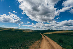 A sandy road through a field Royalty Free Stock Photography