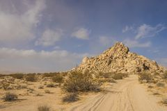 Sandy Road Leads to Boulder Hill. Soft sand road leads through desert to a massive hill made of sandstone boulders Stock Photo