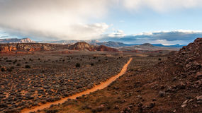 Sandy road through Southern Utah Desert landscape. A sandy trail cutting through the dry desert brush land, with a storm settling in Stock Photos