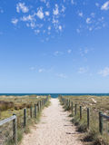 Sandy road to the sea in Australia. Beautiful sandy footpaths to the beach, between two fences of wood and wire and the blue sea in the distance and blue sky Royalty Free Stock Photos