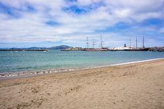 Sandy San Francisco beach looking out across the bay towards docked museum ships stock photography
