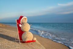 Sandy-Schneemann, der im Strandaufenthaltsraum ein Sonnenbad nimmt. Feiertagskonzept für Ne lizenzfreie stockbilder