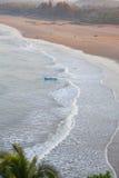 Sandy sea beach and fishermen in a boat. Morning landscape. Sandy sea beach and fishermen in a boat. Gokarna, India Stock Image