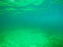 Sandy sea floor under green water in Sardinia Royalty Free Stock Photography