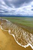 Sandy sea shore on storm Royalty Free Stock Photo