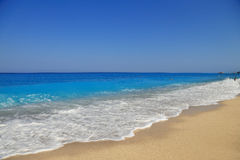 Sandy seashore with blue sky Stock Images