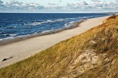 Sandy seashore with cloudy sky Stock Photography