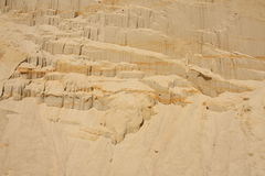 Sandy shore - background. Sandy slope where you can see layers of sediment Stock Images