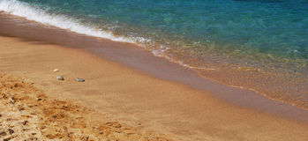 Sandy shoreline. A sandy beach shoreline with three small stones Royalty Free Stock Image