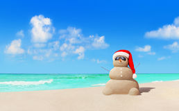 Sandy snowman in Christmas Santa hat and sunglasses at beach royalty free stock photography